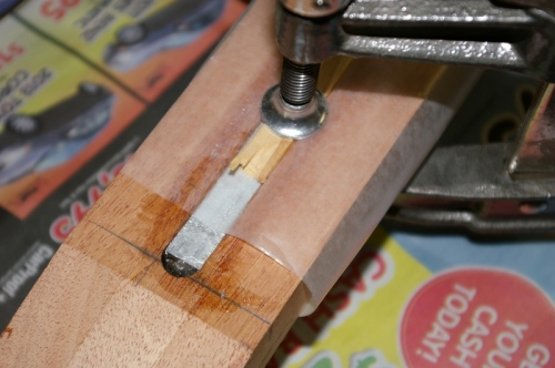 Truss rod with epoxy, wax paper and popsicle stick used as a caul for the clamps